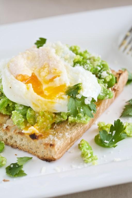 Toast met tuinbonen en een gepocheerd ei stock