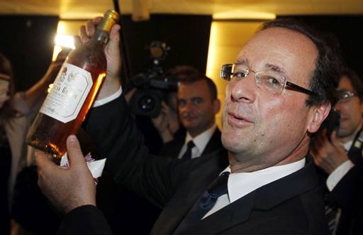 France's newly-elected President Francois Hollande displays a bottle of wine he received during his visit to the General Council of Correze in Tulle
