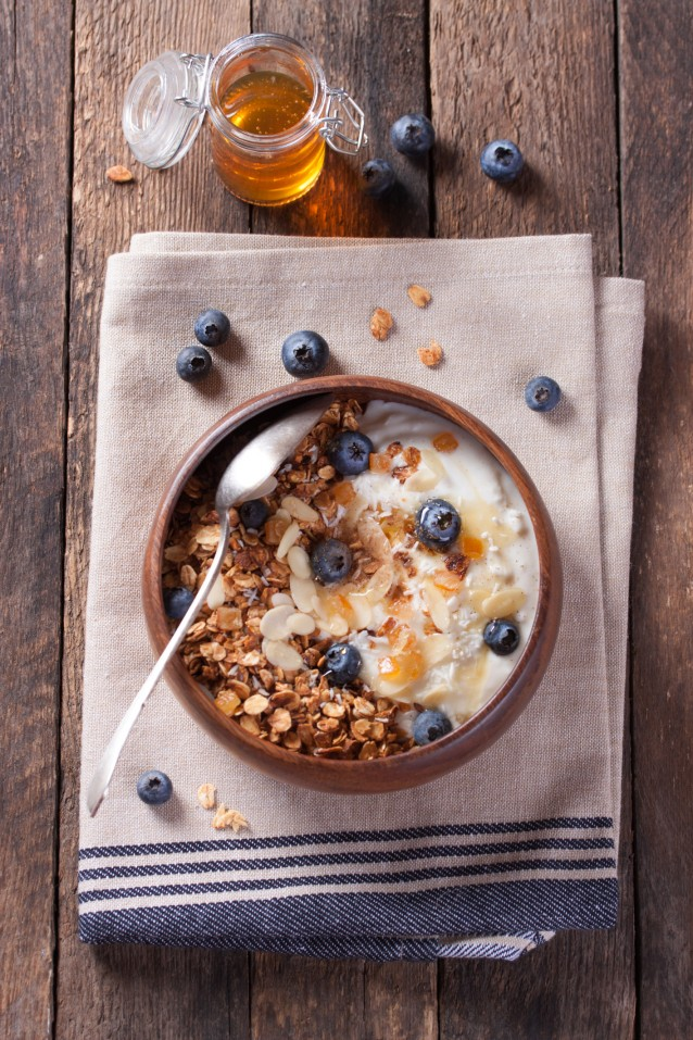 Homemade granola with nuts, candied oranges, fresh blueberries, yogurt