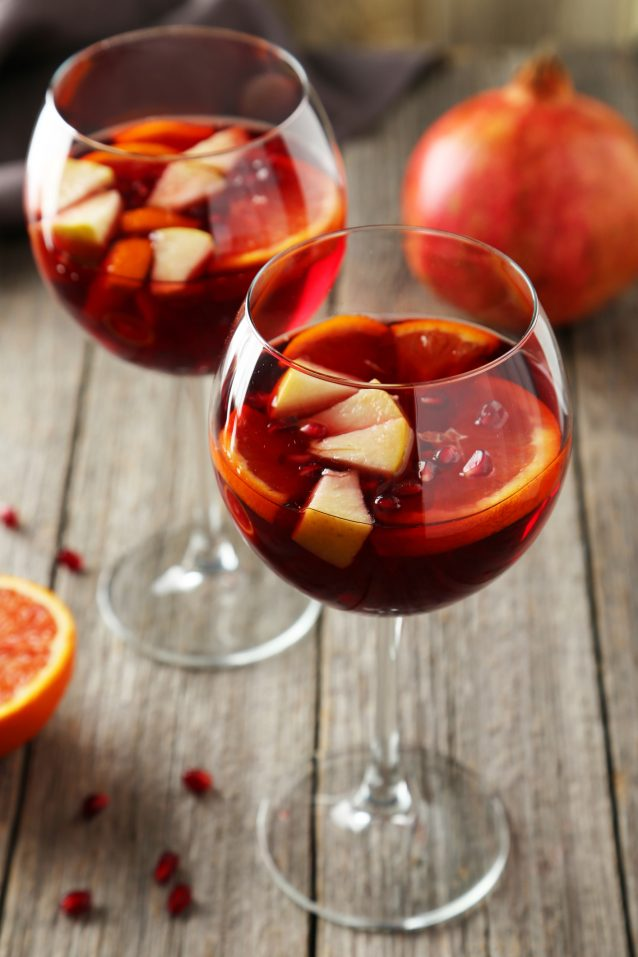 Glasses of sangria on wooden table with pomegranate
