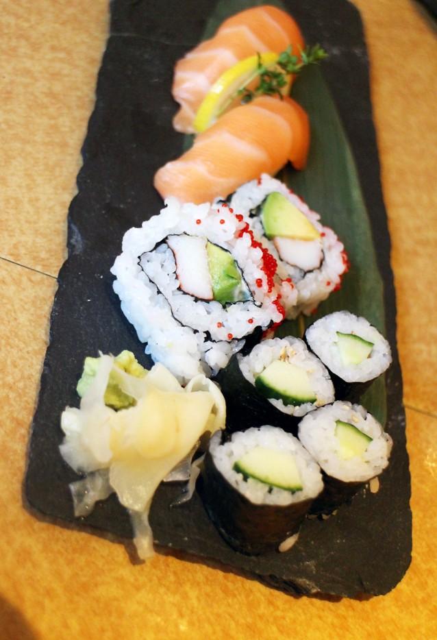 De sushi: nigiri van zalm, california roll en komkommer maki