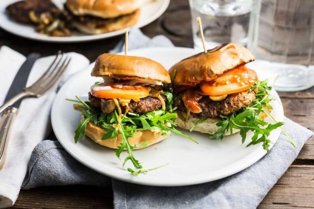 Koken met aanbiedingen zelfgemaakte hamburgers met gebakken champignons