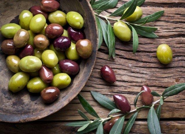 Wooden bowl full of olives and olive twigs.
