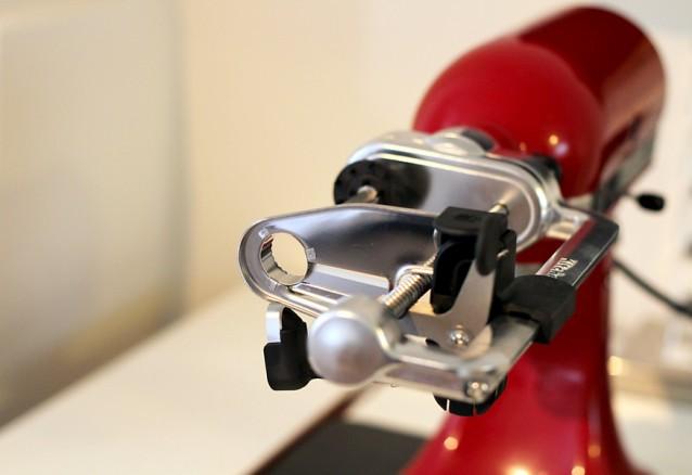 Het opzetstuk, dat je voorop de KitchenAid mixer klikt, met een mes en een schilmes.