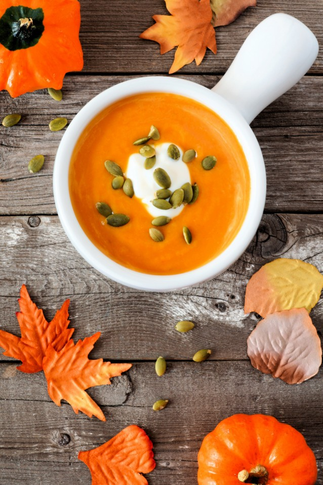 Creamy autumn butternut squash soup on rustic wood background