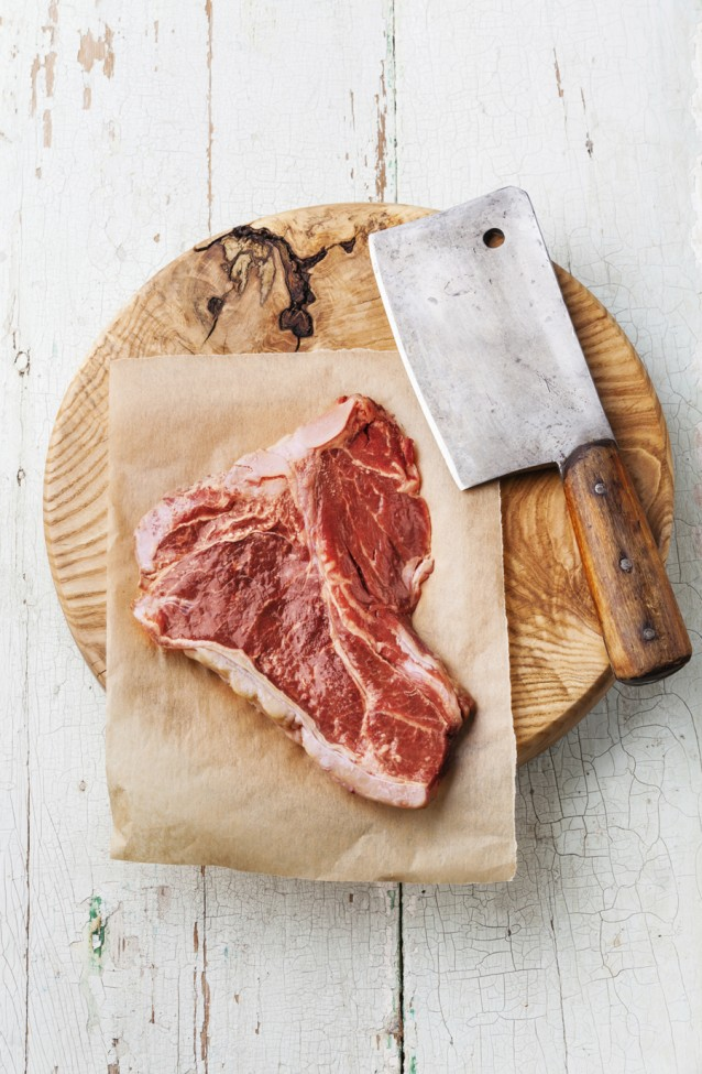 Raw meat T-Bone Steak and meat cleaver