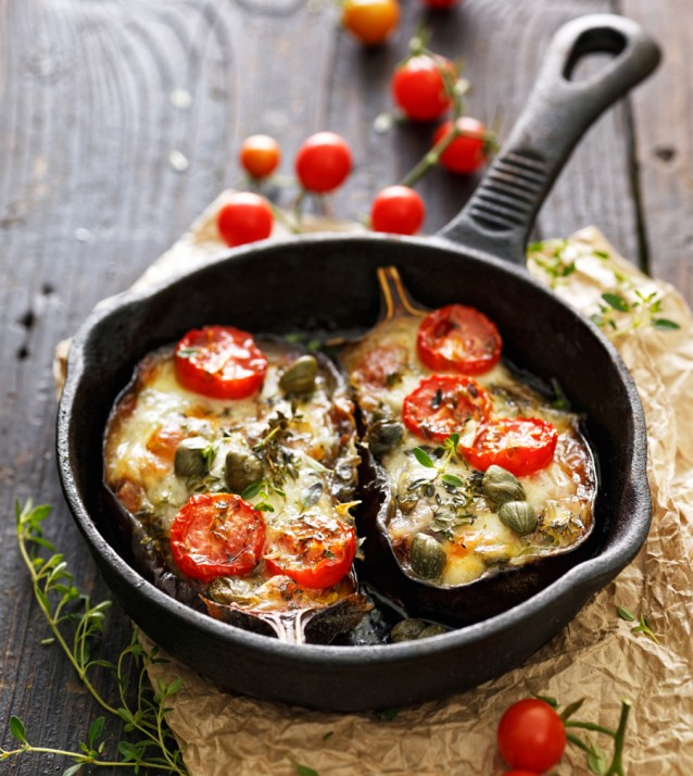 Geroosterde aubergines met tomaten en kappertjes stock
