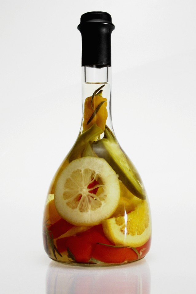 Bottle of olive oil with fruit and vegetables, close-up