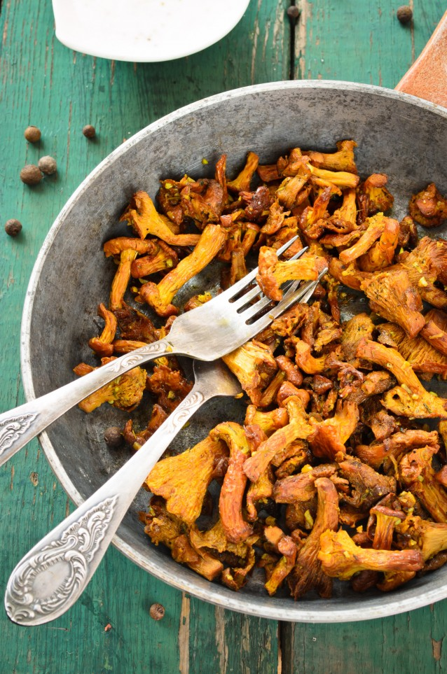 Fried Chanterelles with onions and fresh herbs in skillet