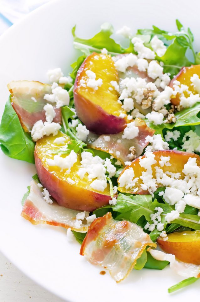 salad with peaches, bacon; arugula, spinach and goat cheese on a light background. toning. selective focus on left peach.