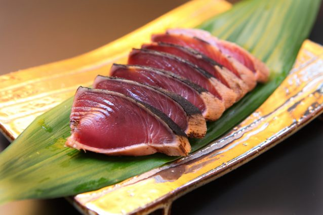 A dish of Katsuo no tataki on leaves