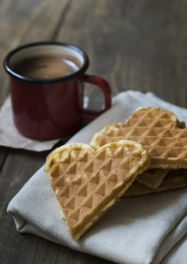 heart shaped waffles and coffee on table in close up