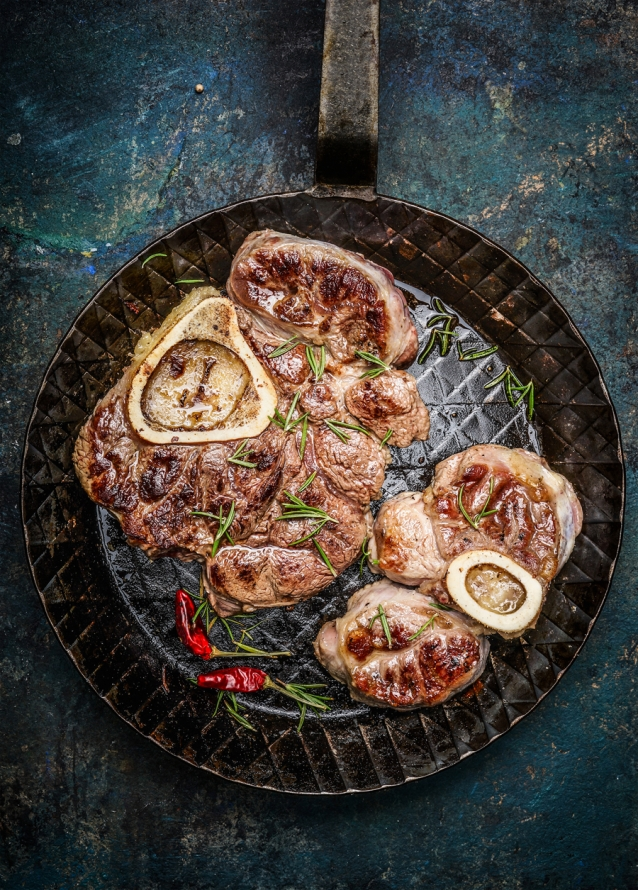 Roasted veal shank slices in frying pan on rustic background