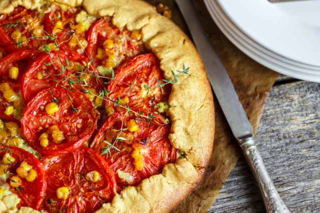 Homemade summer outdoor pie with tomatoes, corn and thyme. Galette