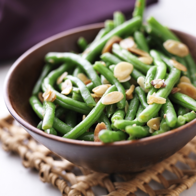 close up photo of a bowl of green beans with almonds