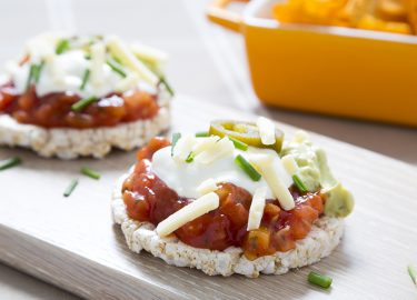 Rice cakes topped with tomato salsa, gaucamole, sour cream, grated cheddar cheese, jalapeno peppers and chopped chives. Tortilla style crisps are in the background