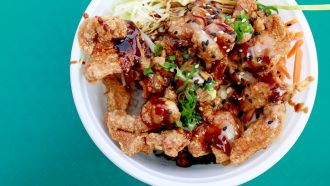 Deep fried chicken basked in teriyaki sauce with vegetables, spice, and rice.