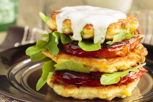 Corn fritters stacked with roasted tomatoes and arugula, served with ranch dressing