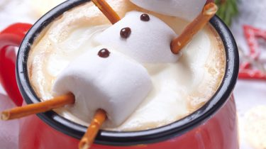 Red mug with hot chocolate with melted marshmallow snowman
