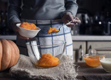 pompoenpuree Putting pumpkin puree in the glass bowl horizontal