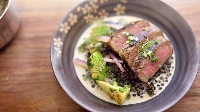 Een gegrilde New York strip steak met een warme linzensalade