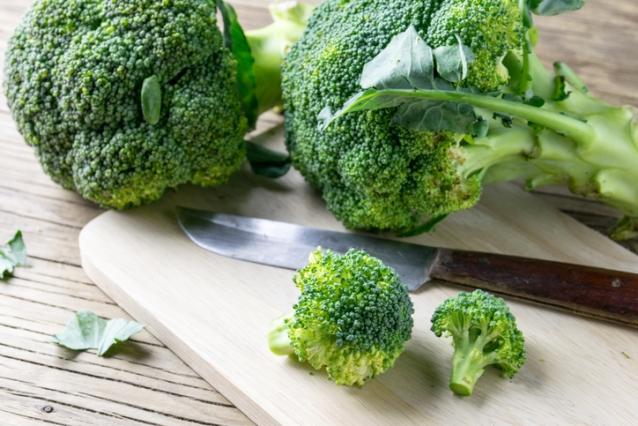 fresh broccoli on a cutting board and knife