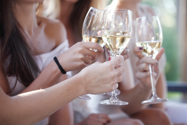 Happy female friends toasting white wine outdoors
