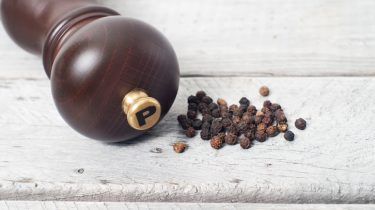 Pepper mill and black peppercorn against wooden table