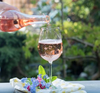 Waiter pouring a glas of cold rose wine, outdoor terrase, sunny day, green garden background