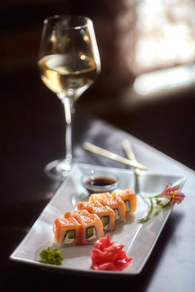 Philadelphia maki sushi rolls with salmon, cheese cream, cucumber on white plate and glass of wine