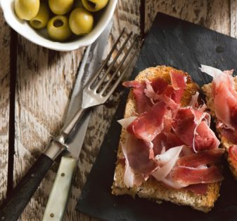 Delicious appetizer of spanish ham and salad, on rustic table