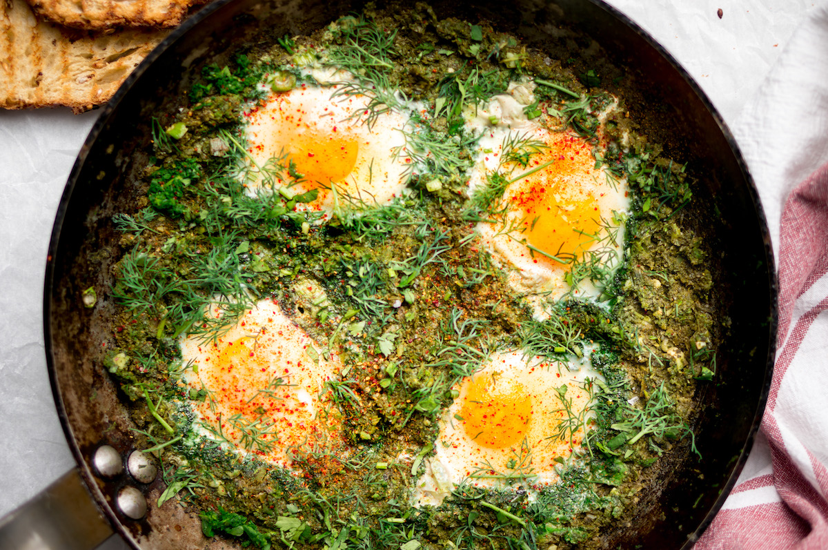 Groene shakshuka met spinazie en toast voor lunch op kantoor