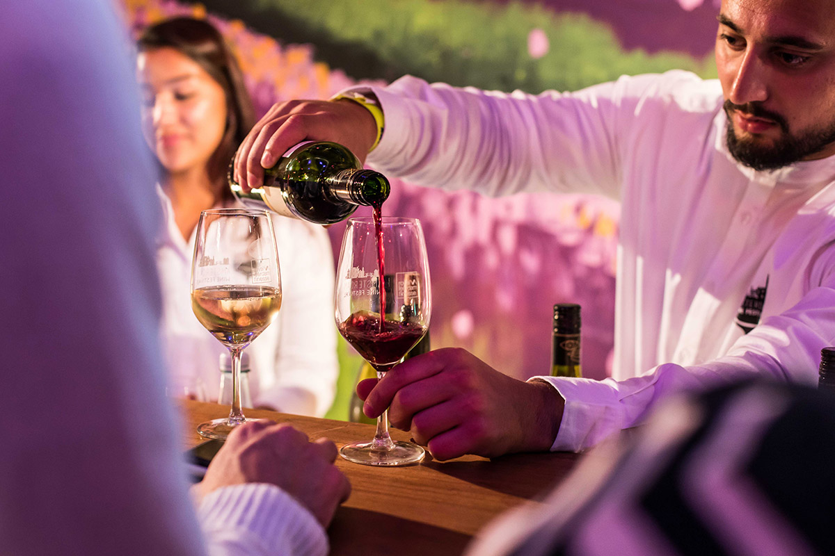 man schenkt een glas wijn in
